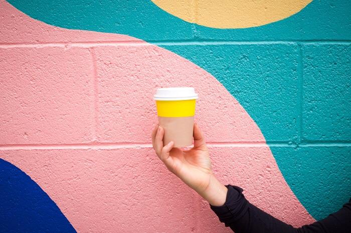 Frau hält einen Coffee-To-Go Becher